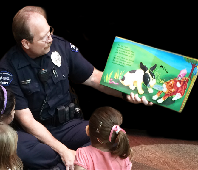 "Officer Jim Hill reads to children at a previous ""Book'Em"" reading event."