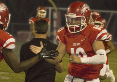 Quarterback Ratheen Ricedorff celebrating with other Mesa Football players during blowout victory against Phoenix.