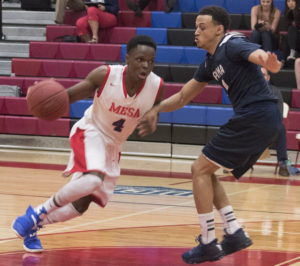 Obi Megwa drives down the court while Pima opposition stands in his way.